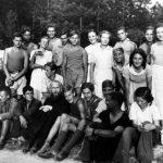 """Tábor """"Rytířů"""" (některé děti v uniformovaných košilích s kravatou). Léto, konec 30. let 19. století, nebo začátek války. Uprostřed skupiny otec Michail se synem Viktorem. """"Rytíři"""" (rusky «Vitjazi») byla dětská společenská organizace, založená v prostředí ruského zahraničí v 30. letech. Jejím cílem byla výchova dětí ruských emigrantů v cizině v duchu ruských tradic, uchování a předávání odkazu předsovětského Ruska."""